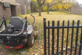Riding mower in residential complex back yard.