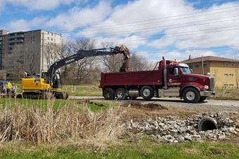 Loading JB Landscape dump truck at path and culvert installation.