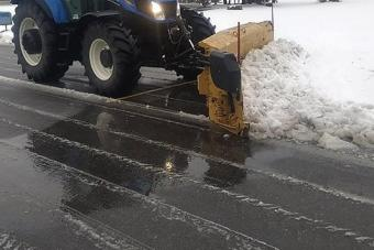 Tractor with a plow blade on the front plowing a road.