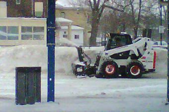 A Bobcat plowing snow.